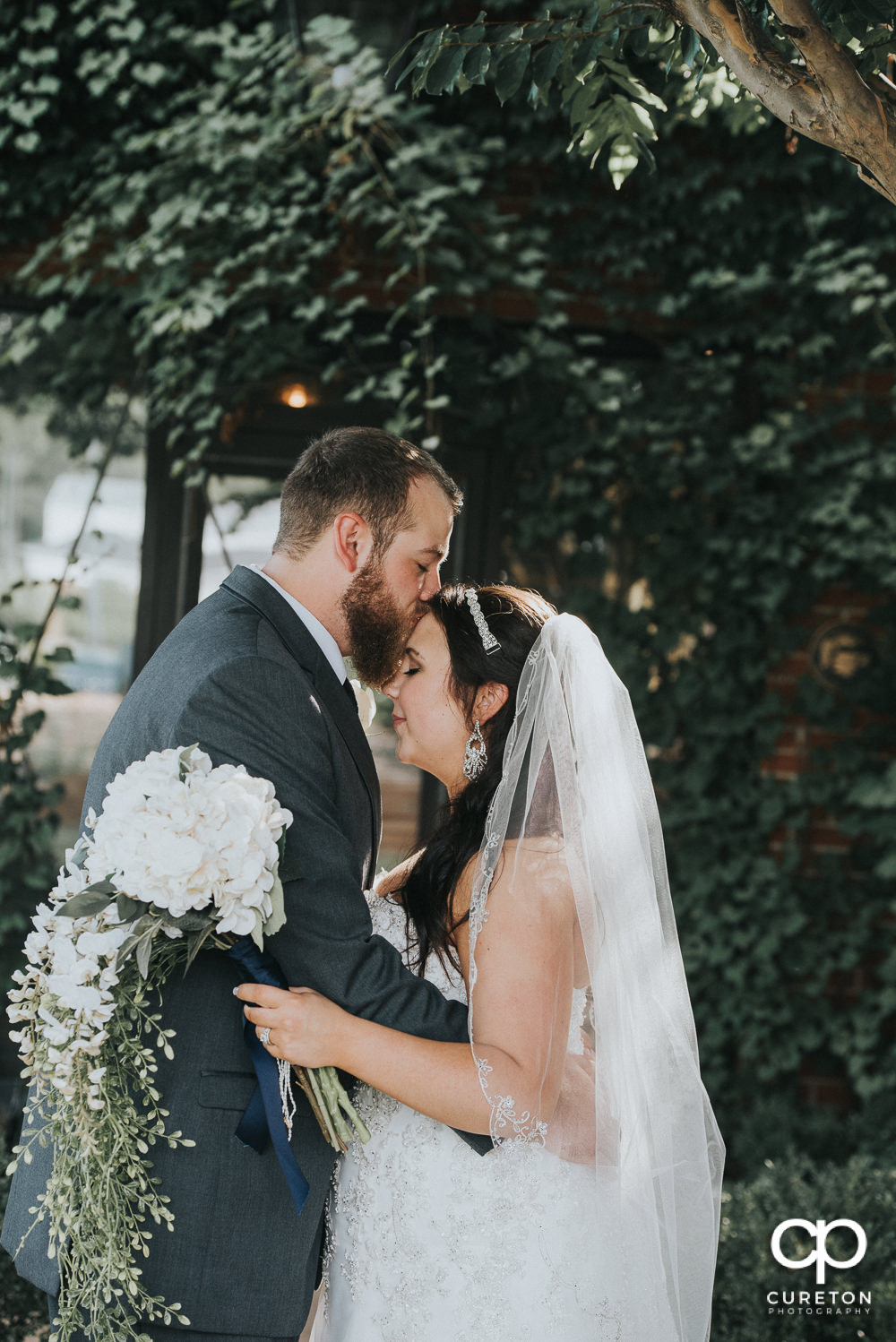 Groom kissing his bride on the forehead in front of a wall of ivy at The Loom after their wedding.
