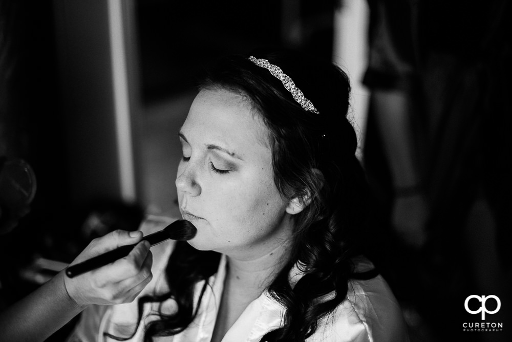 Bride getting makeup applied.