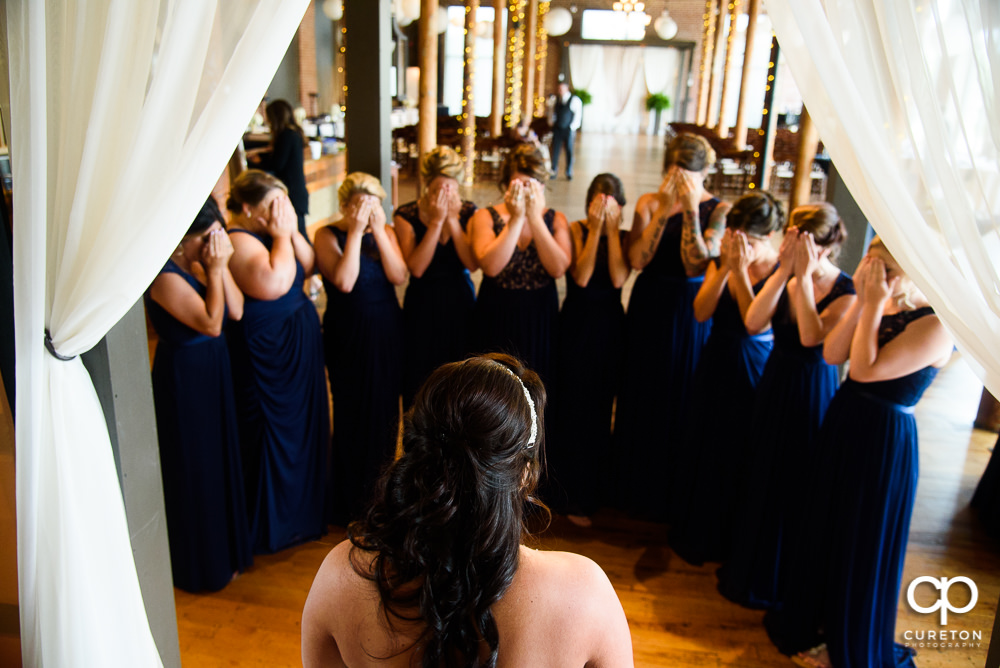 Bride ready to reveal herself in the dress to her bridesmaids.