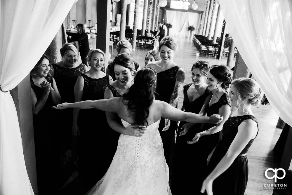 Bridesmaids hugging the bride.