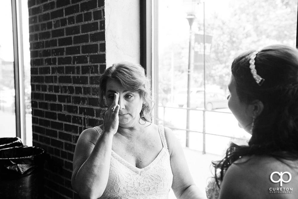 Bride's mom crying when she sees her daughter.