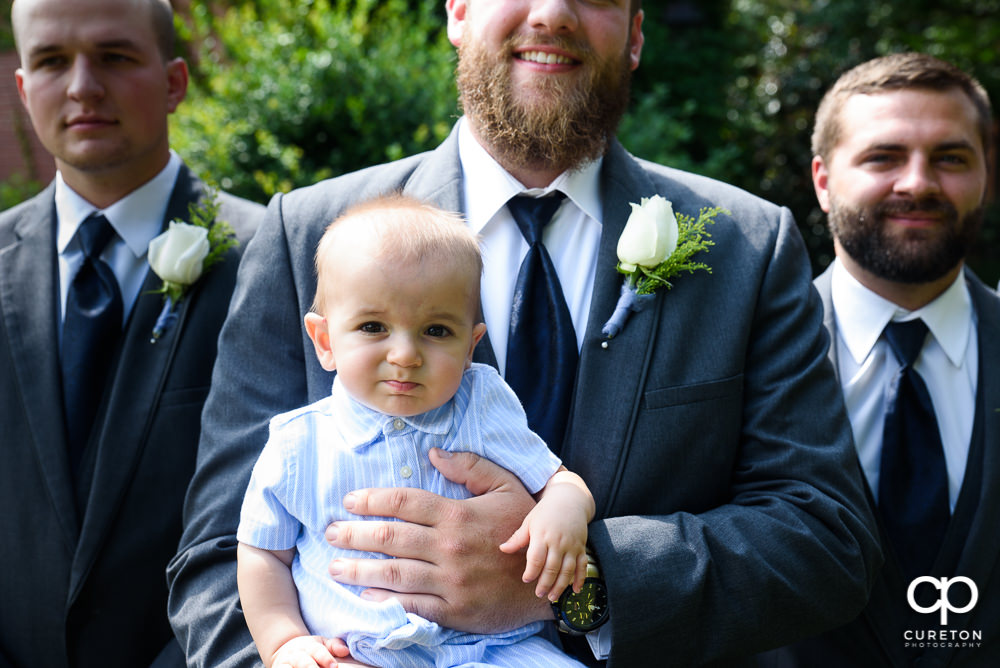 Groom holding his infant son.