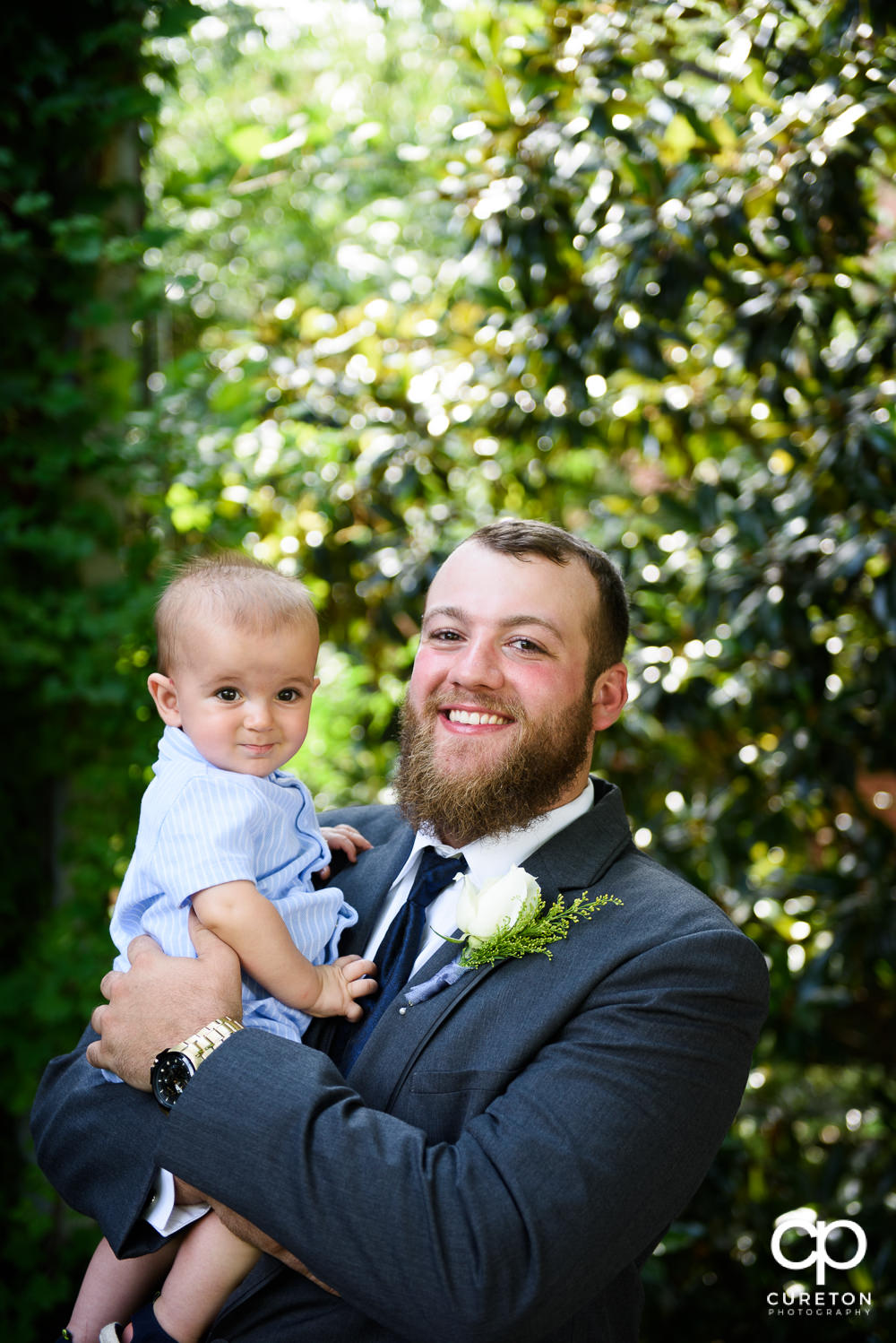 Groom kissing his infant son.