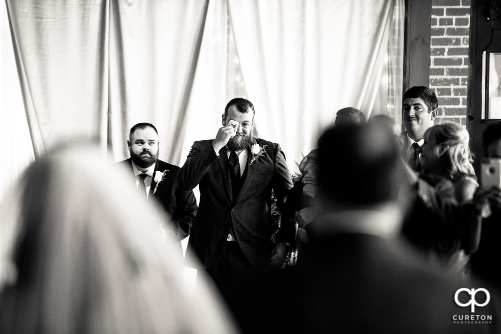 Groom tearing up as he sees his bride for the first time walking down the aisle during their wedding ceremony at The Loom at Cotton Mill Place.