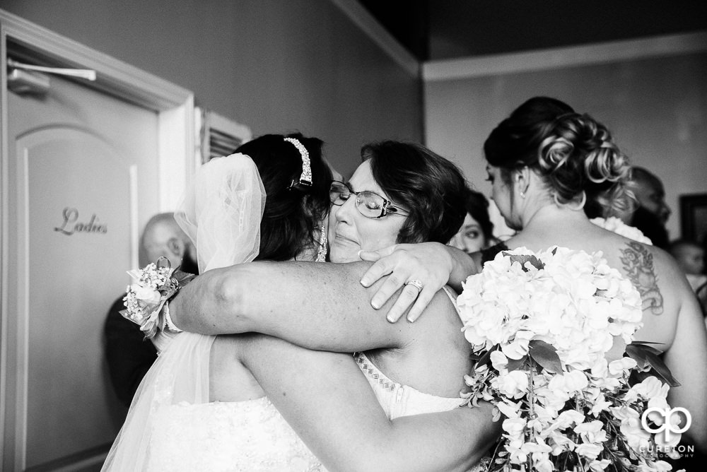 Bride and her mom hugging after the wedding.