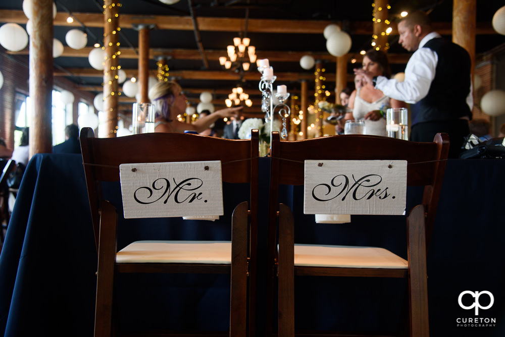 Mr. and Mrs. sign on the back of chairs.