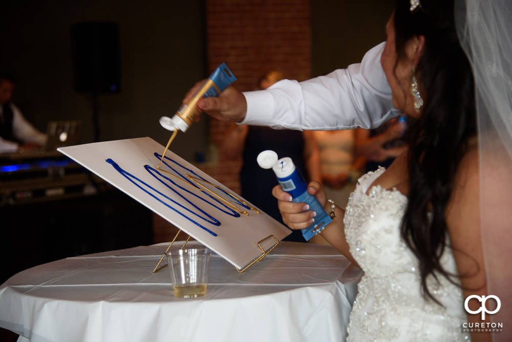 Bride and groom performing a paint ceremony at the reception.