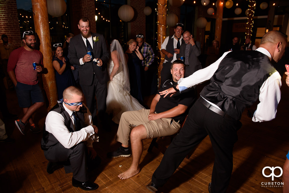 Person who caught the garter putting it on the person who caught the bouquet.