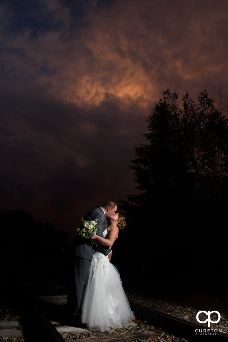 Bride and groom kissing with a purple sunset during their wedding reception at The Old Cigar Warehouse.