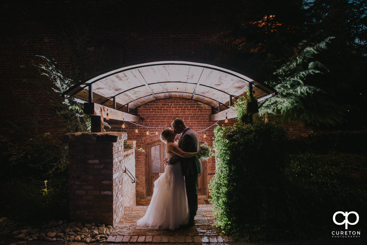 Bride and Groom kissing with twinkle light sin the background at night at their Old Cigar Warehouse wedding.
