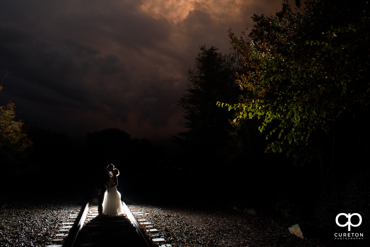 Married couple standing on the railroad tracks at sunset at The Old Cigar Warehouse.