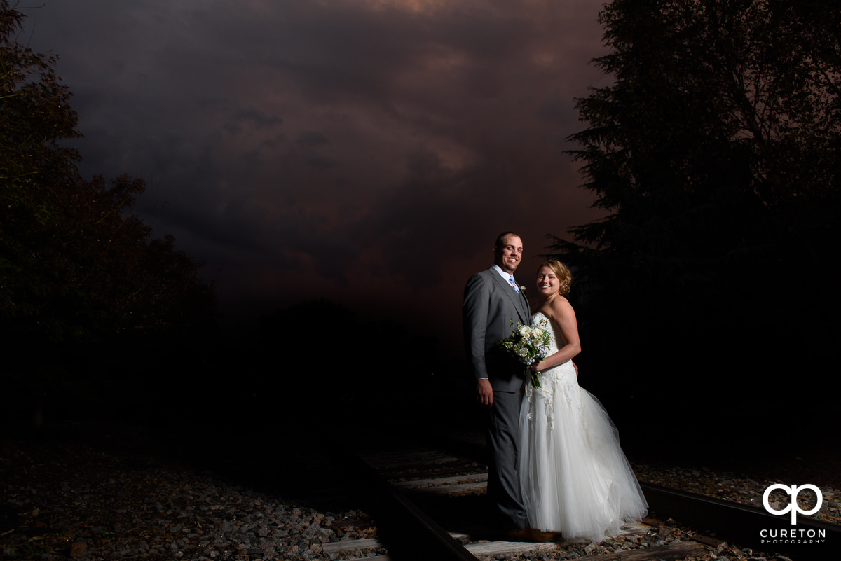 Couple standing on the railroad tracks at sunset during their Old Cigar Warehouse wedding.