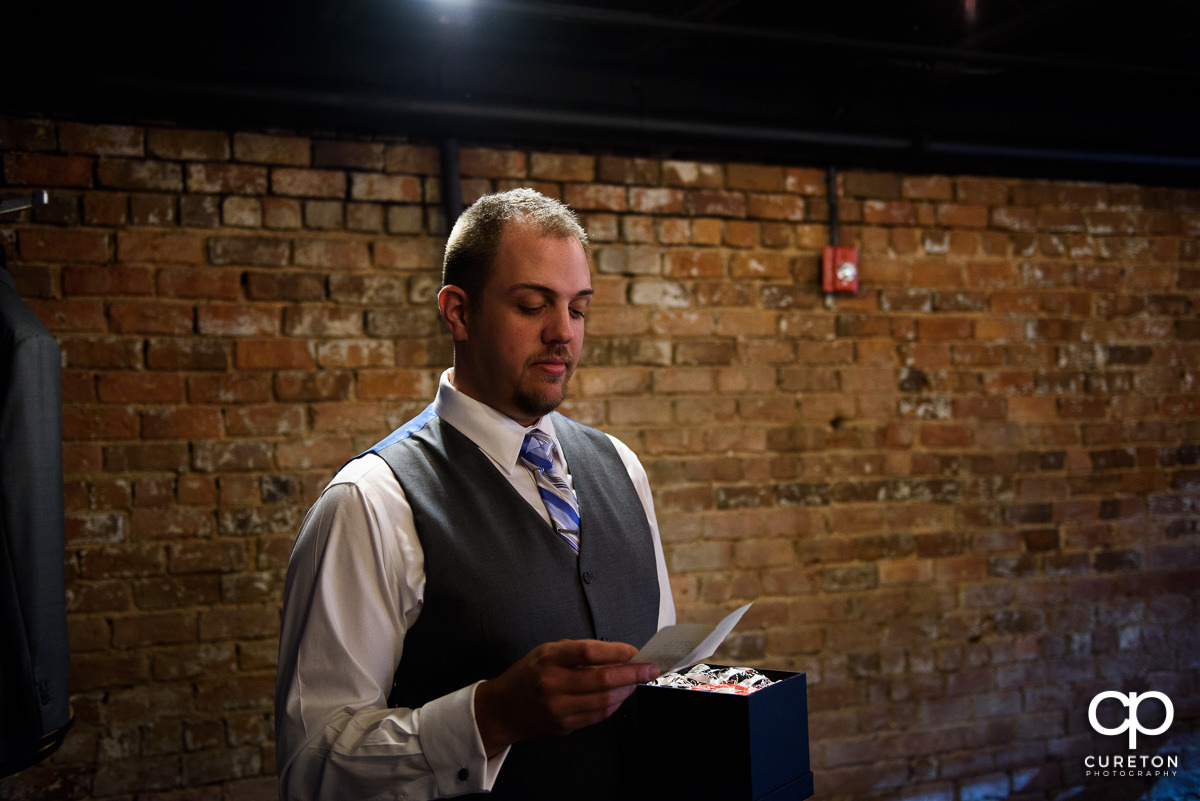 Groom reading a note from his bride.