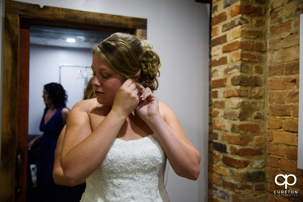 Bride putting earrings in.