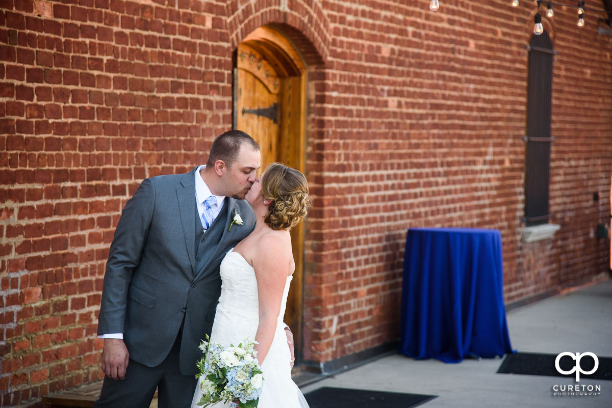 Groom kissing his bride at their first look.