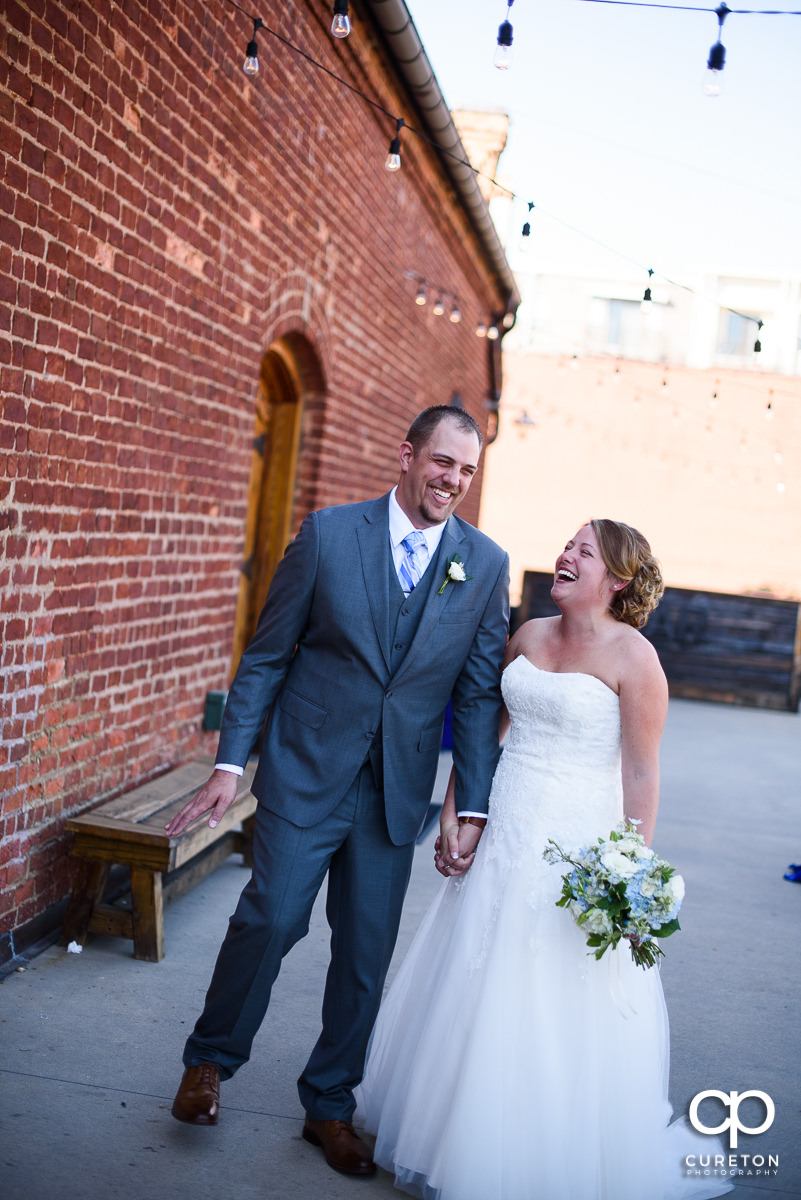 Bride and groom laughing before their wedding at Old Cigar Warehouse.