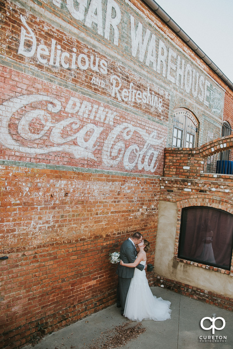 Bride and groom kissing at The Old Cigar Warehouse.
