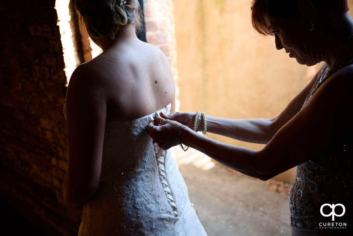 Bride getting her dress zipped up.