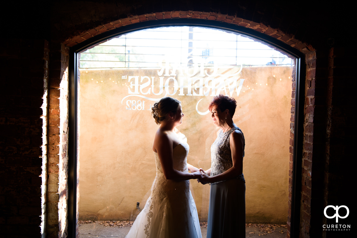 Bride and her mother holding hands before the wedding ceremony at The Old Cigar Warehouse.