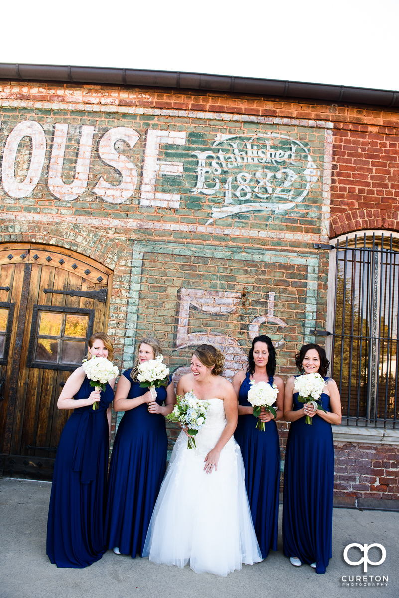 Bride and her bridesmaids laughing on the deck before the wedding at The Old Cigar Warehouse.