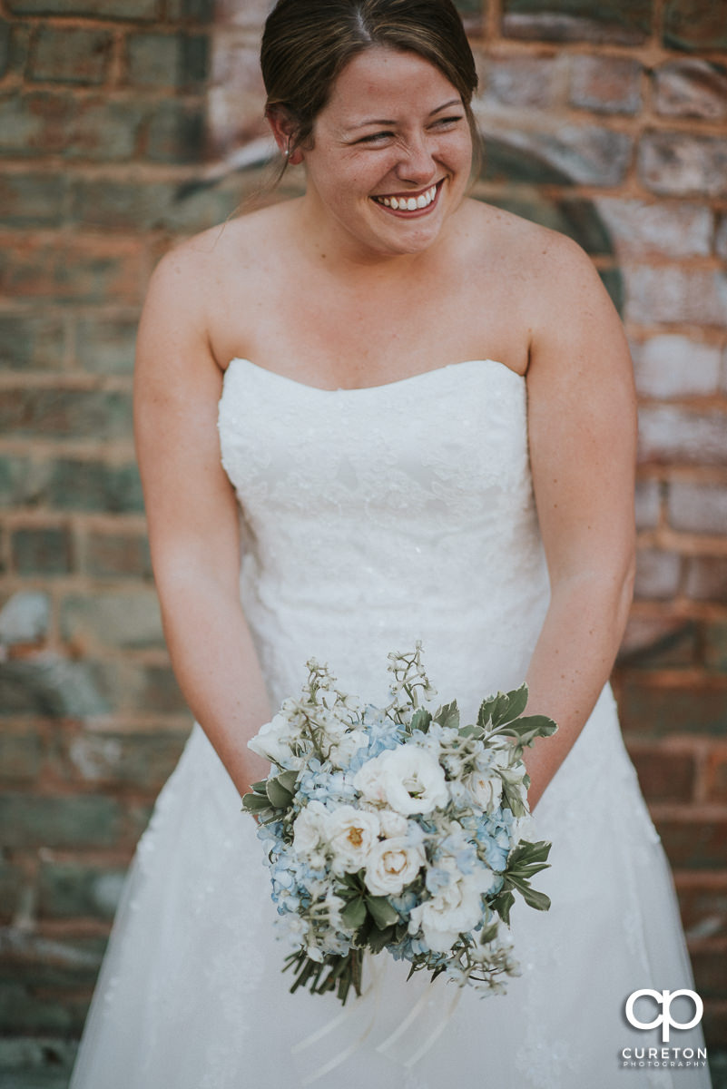 Bride laughing while holding a beautiful bouquet.