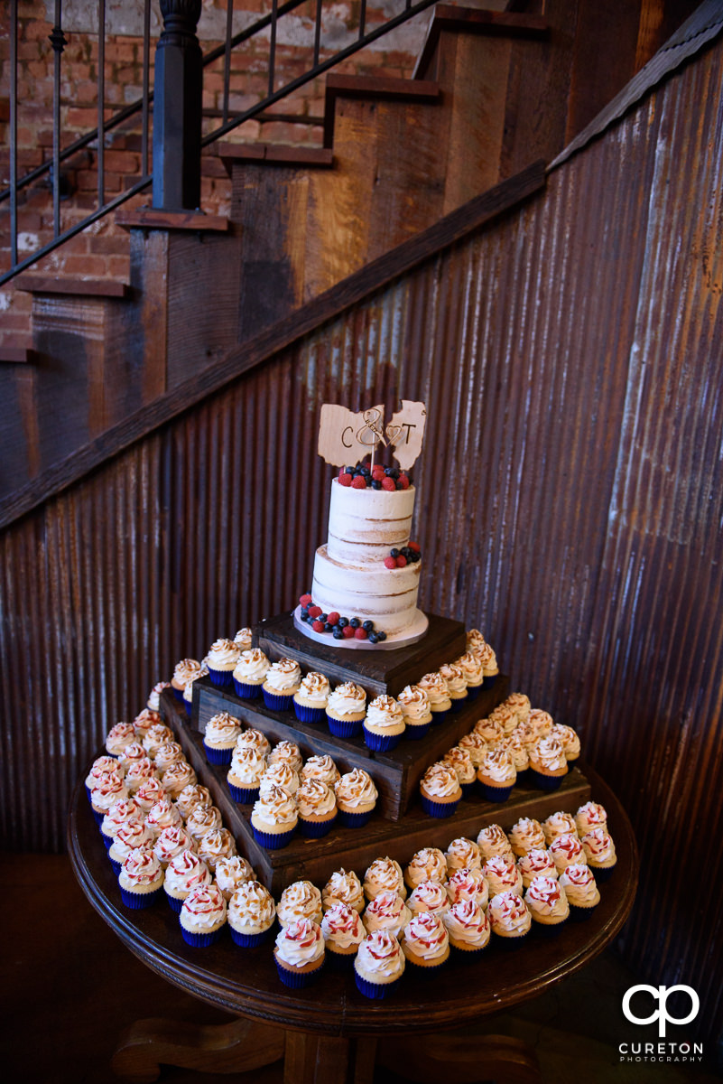 Wedding cake and cupcake display by Buttercream Bakehouse at The Old Cigar Warehouse.