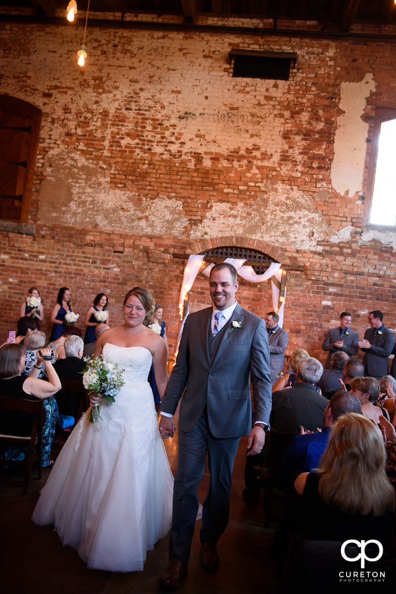 Bride and groom walking down the aisle at The Old Cigar Warehouse.
