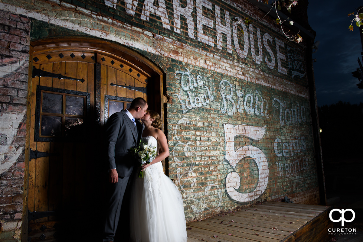 Bride and Groom kissing at night outside the Old Cigar Warehouse.