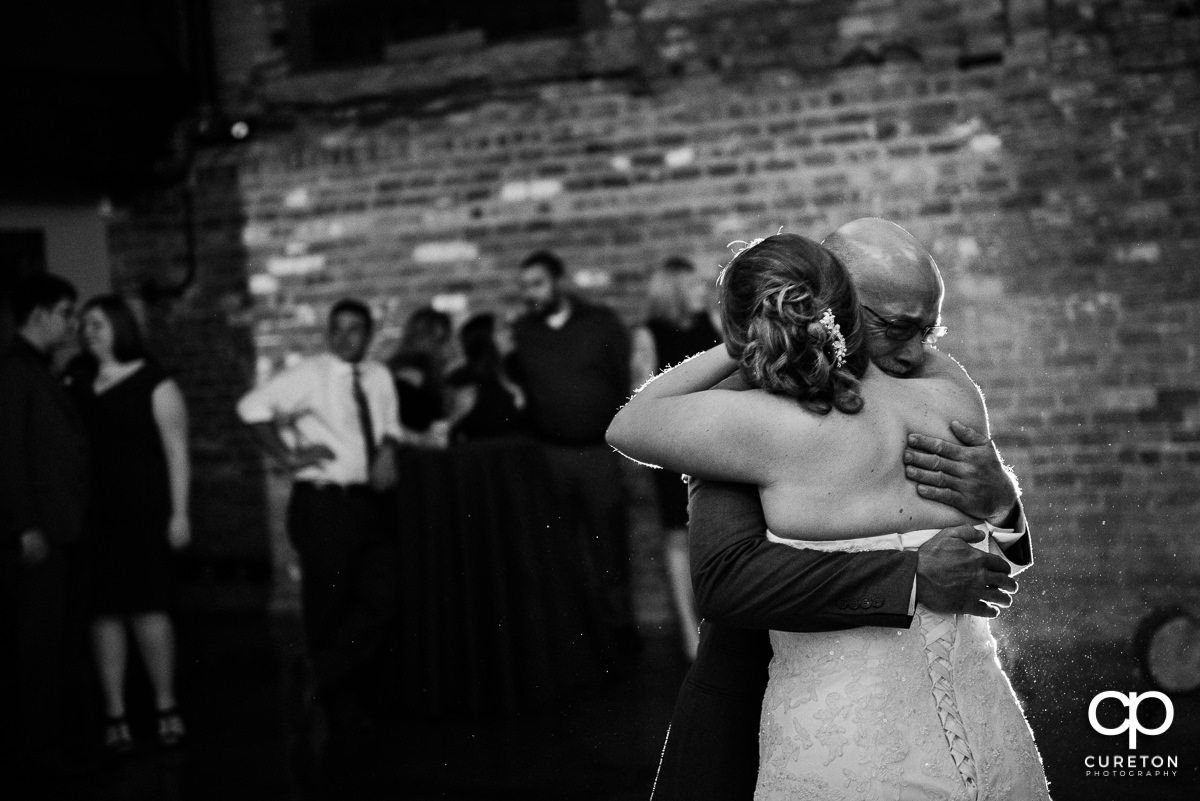 Bride and her dad hugging.