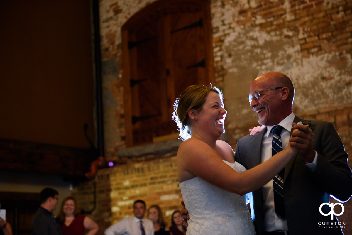 Bride and her father laughing during their dance at the reception.