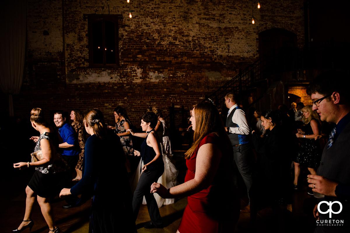 Wedding guests line dancing.