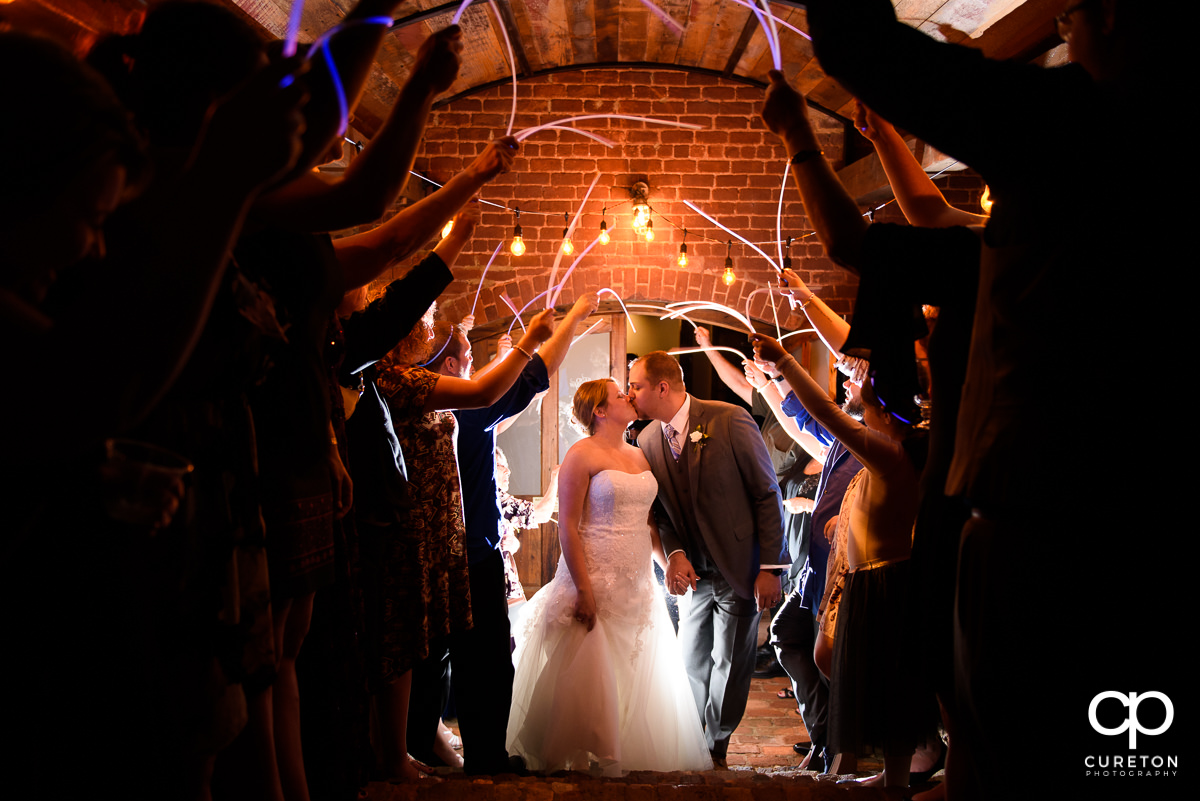 Bride and Groom making an epic grand exit through glow sticks at The Old Cigar Warehouse in downtown Greenville.