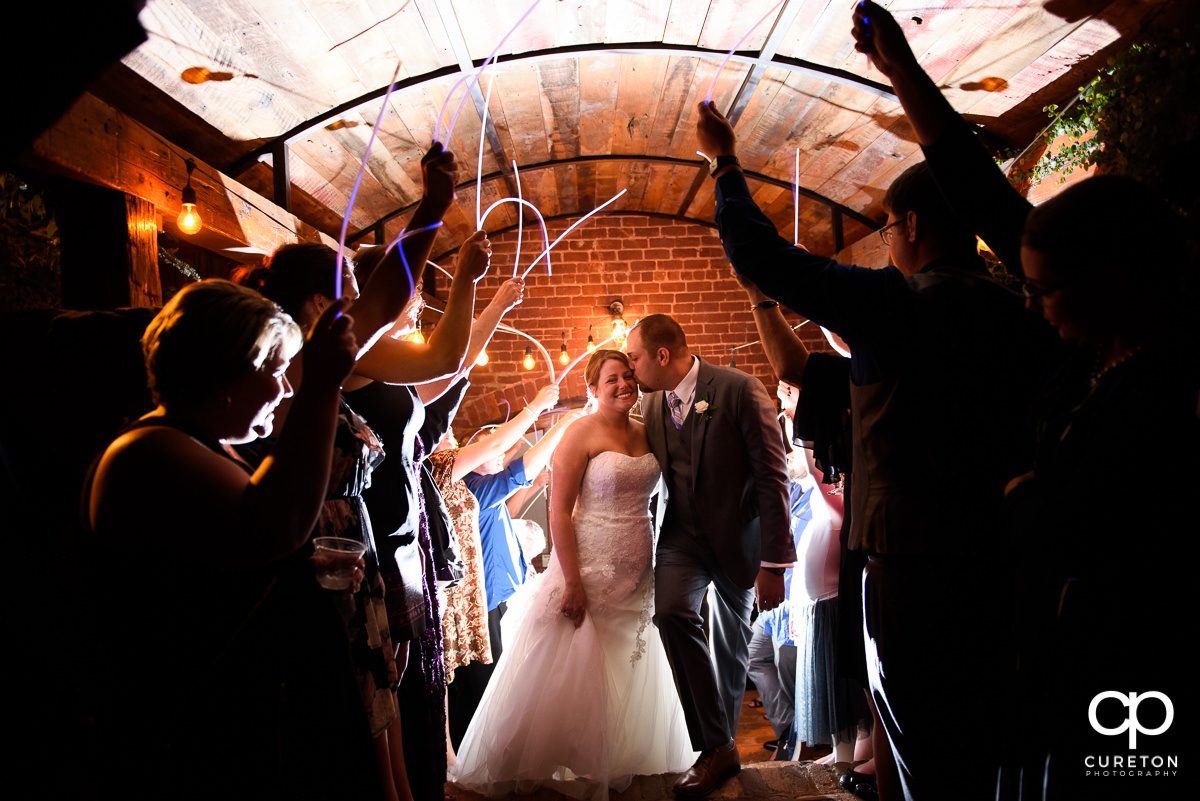 Bride and Groom making an epic grand exit through glow sticks at The Old Cigar Warehouse.