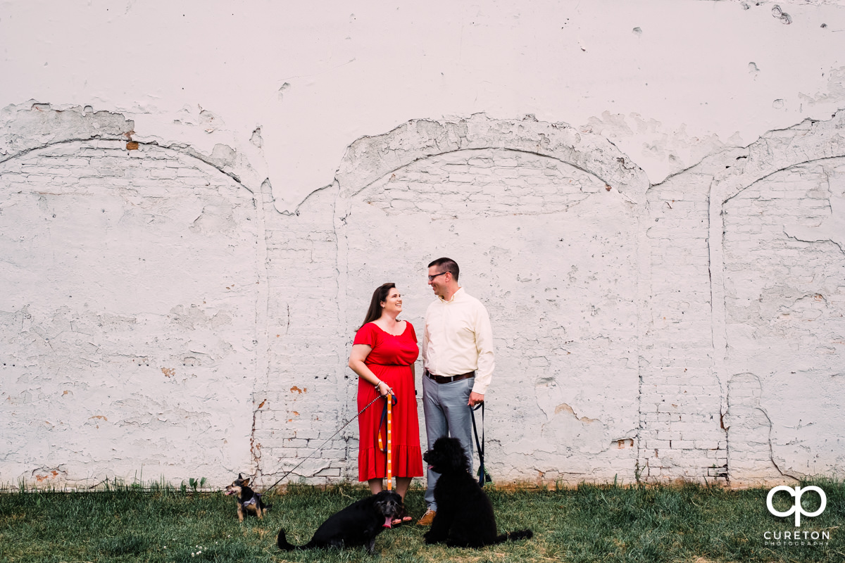 Future bride and groom walking downtown with their dogs during an engagement session in West End Greenville,SC.