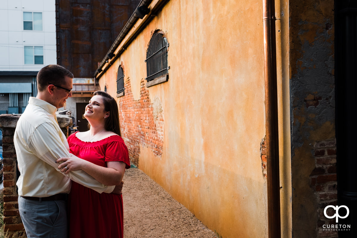 Engaged couple dancing outside of Husk Greenville during and engagement session.
