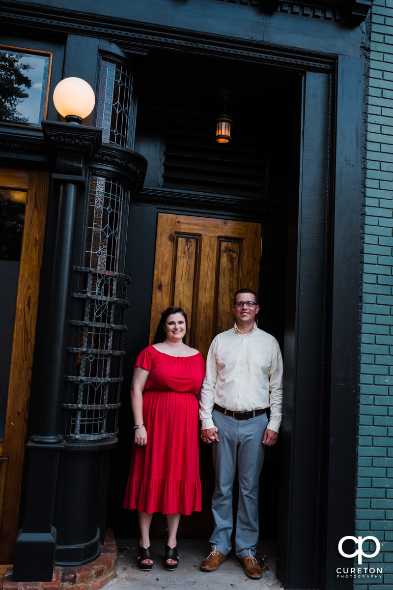 Engaged couple standing outside of Husk in downtown Greenville,SC.