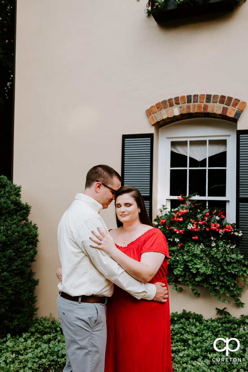 Engaged couple standing in front of Mary's Cottage at Falls Park in downtown Greenville,SC.
