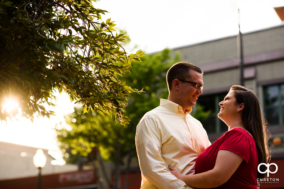 Future bride and groom backlit by warm sunlight during an engagement session in West End Greenville,SC