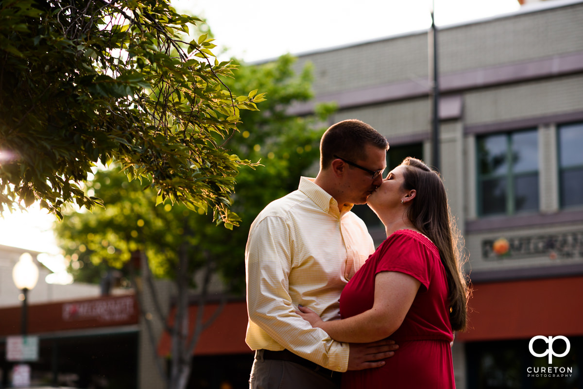 Engaged couple kissing on Main Street Greenville.