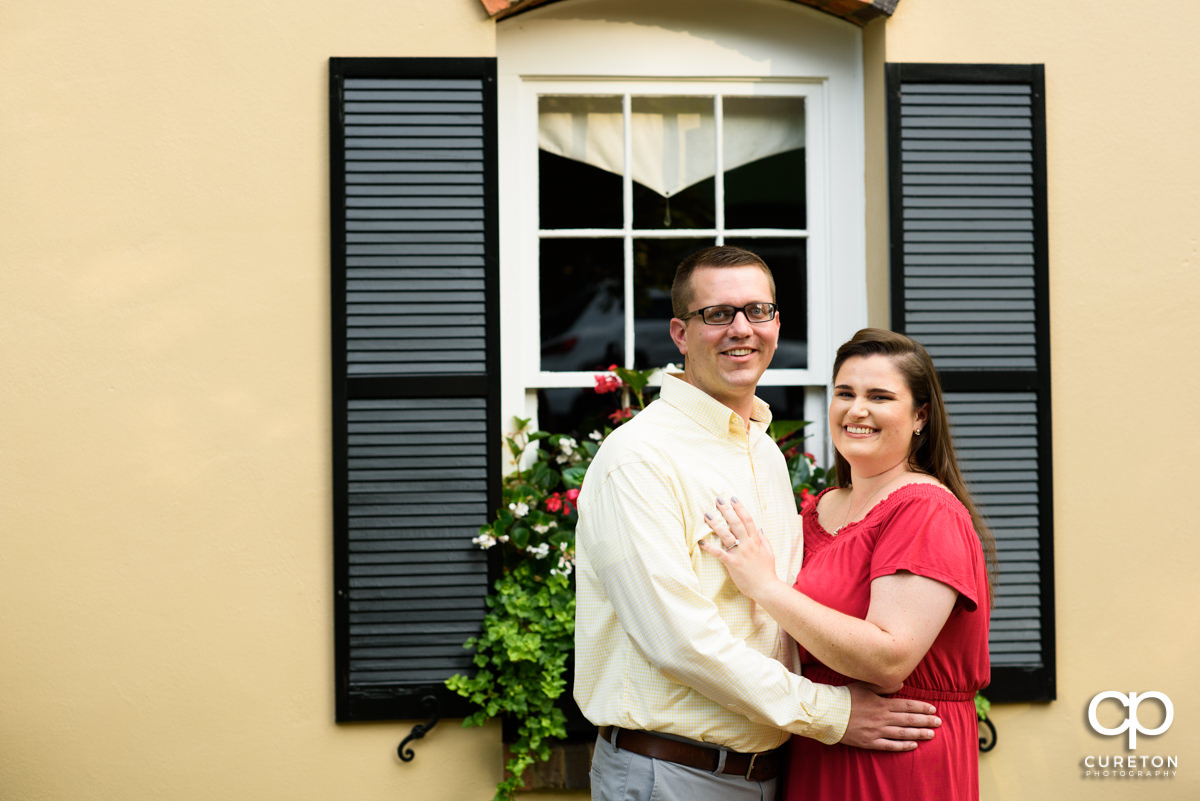 Future bride and groom in front of Mary's cottage at Falls Park.