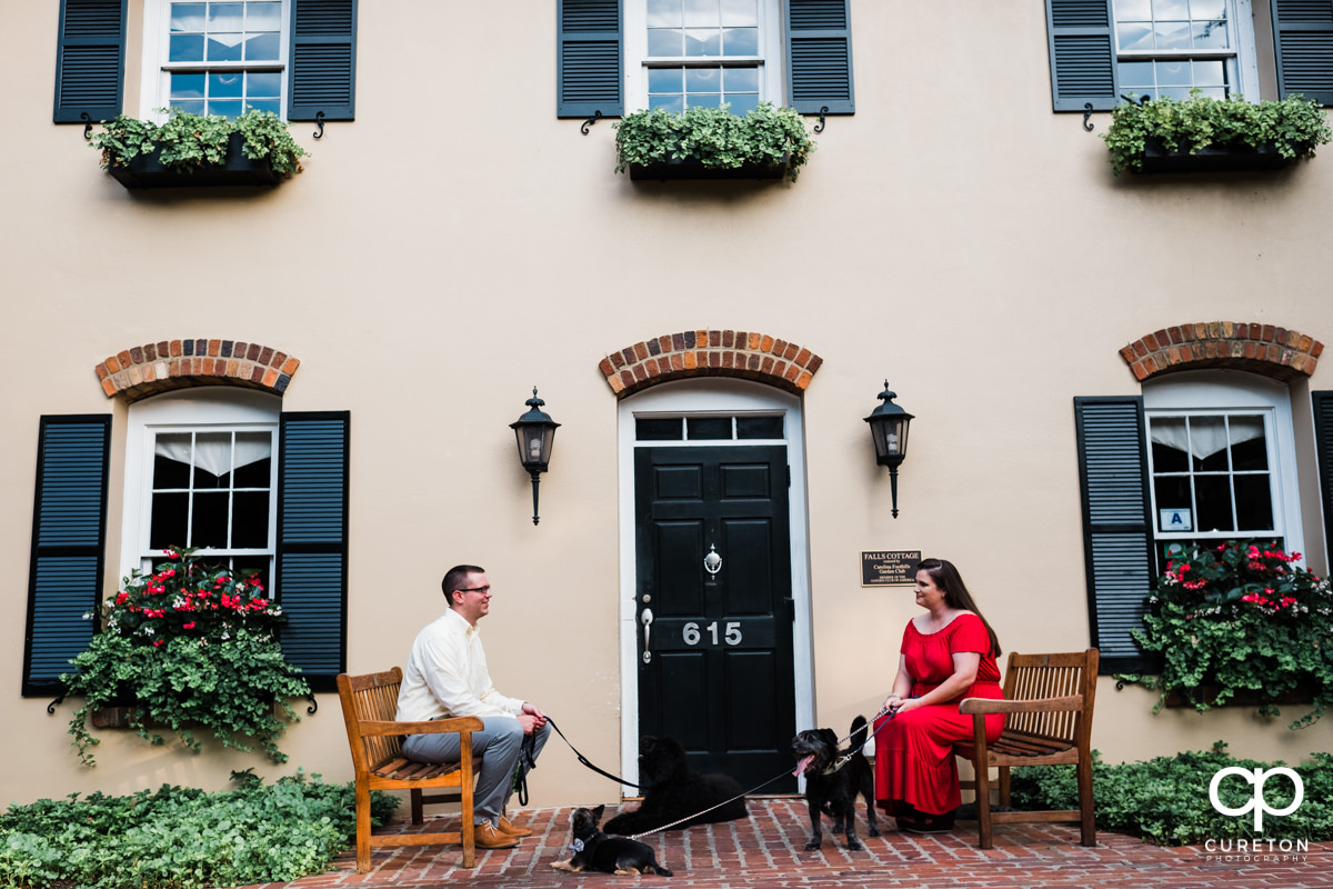 Man and woman with their dogs in front of Mary's cottage in downtown Greenville,SC.