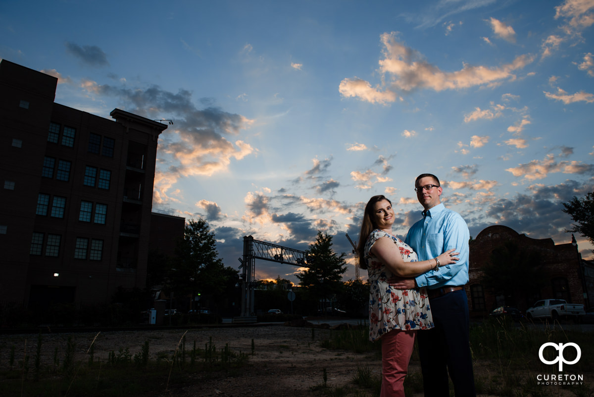Engaged couple strolling though west end Greenville SC at sunset during an engagement session.