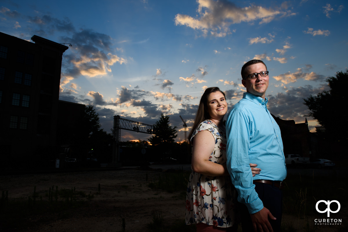 Future bride and groom cuddling at sunset during an engagement session in West End Greenville,SC