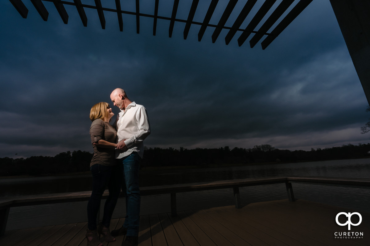 Engaged couple dancing by the lake during a Furman University Engagement session in Greenville,SC.
