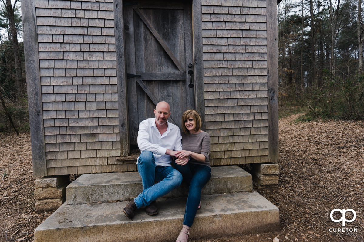 Man and woman sitting on the steps of a rustic cabin during a Furman University winter Engagement session in Greenville,SC.
