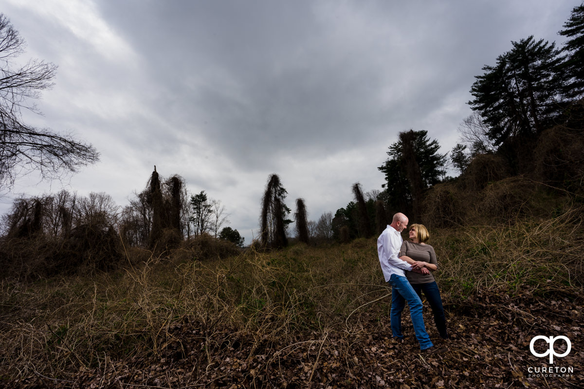 Engaged couple standing in an overgrown field during a Furman University winter Engagement session in Greenville,SC.