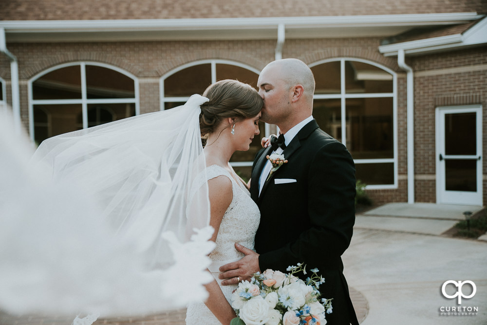 Groom kissing his bride on the forehead as her long veil blows in the wind.