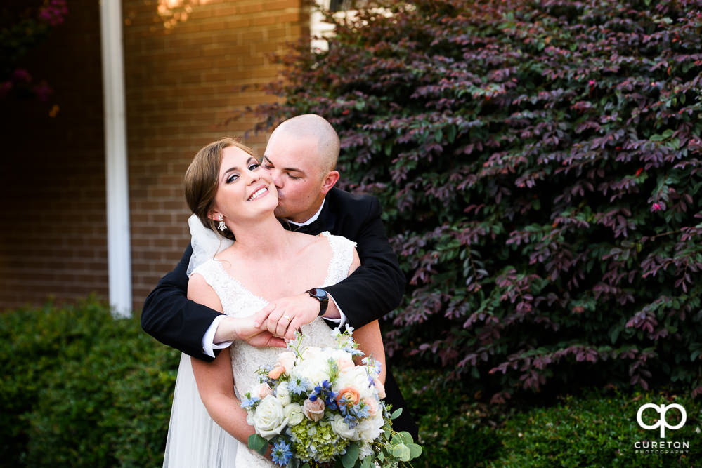 Groom kissing his bride on the cheek after their wedding ceremony.