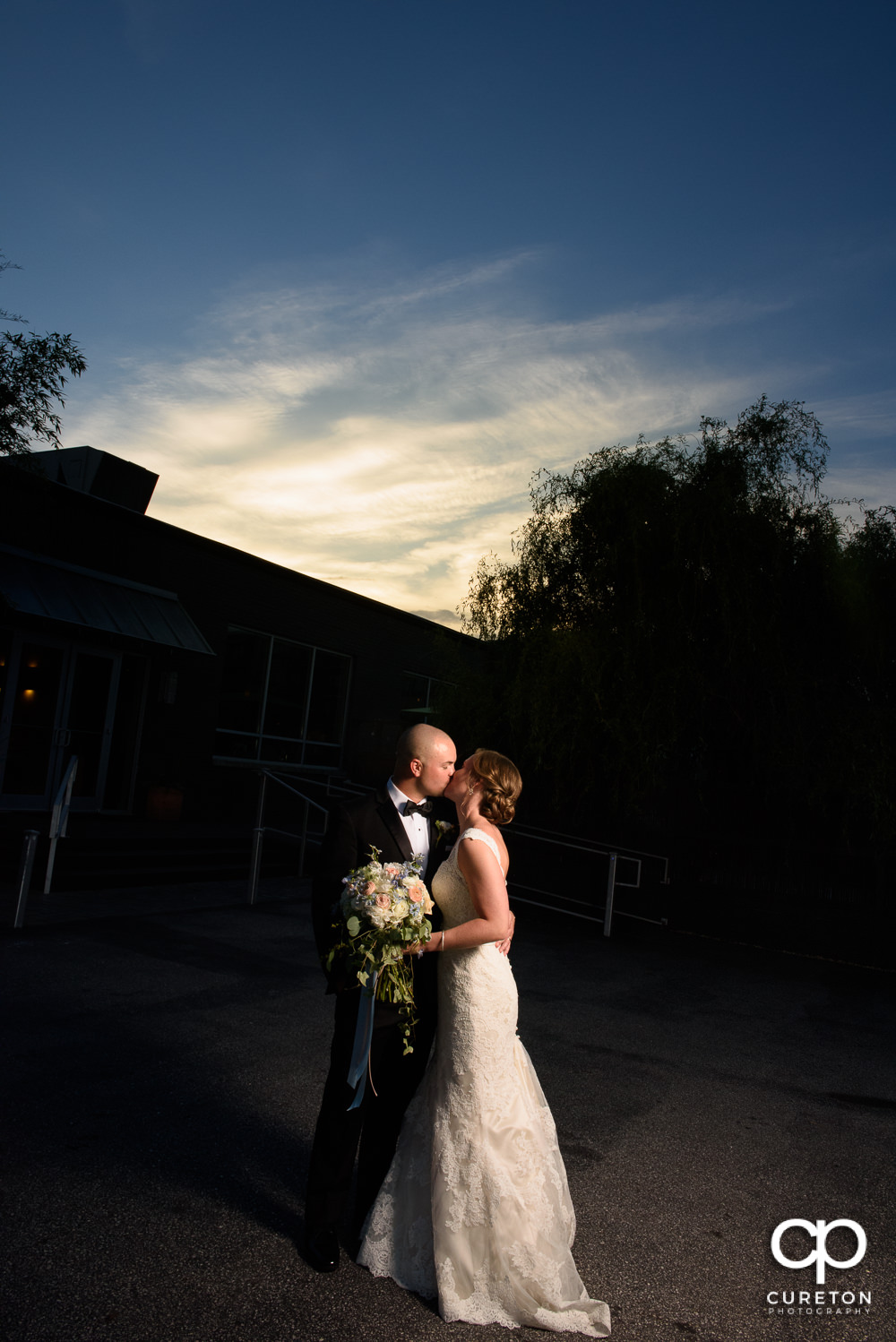 Bride and groom kissing at sunset during their wedding reception at Zen Greenville.