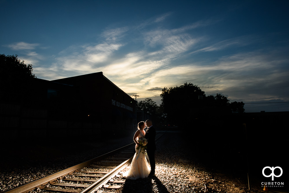 Bride and groom at sunset on the railroad tracks during their wedding reception at Zen Greenville.